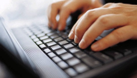 hands typing on a laptop keyboard to illustrate how to win an online car sweepstakes